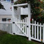 Scalloped picket fence with gate and arbor with colonial post caps in American Fork, Utah